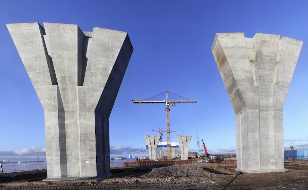 Bridge under construction, massive reinforced concrete support on building site.